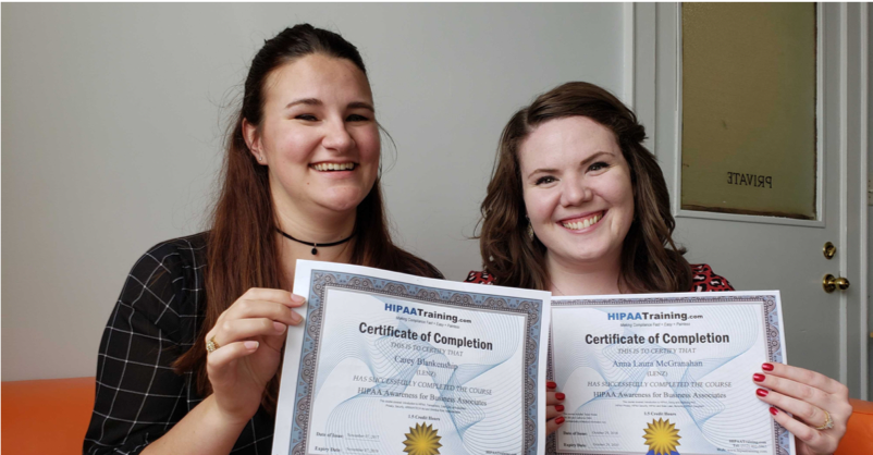 Two Lenz team members, Anna Laura and Carey, hold up their certifications.