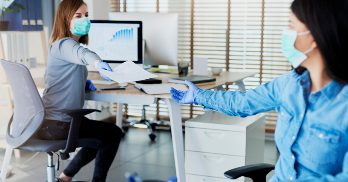 Two physicians working in an office wearing masks.