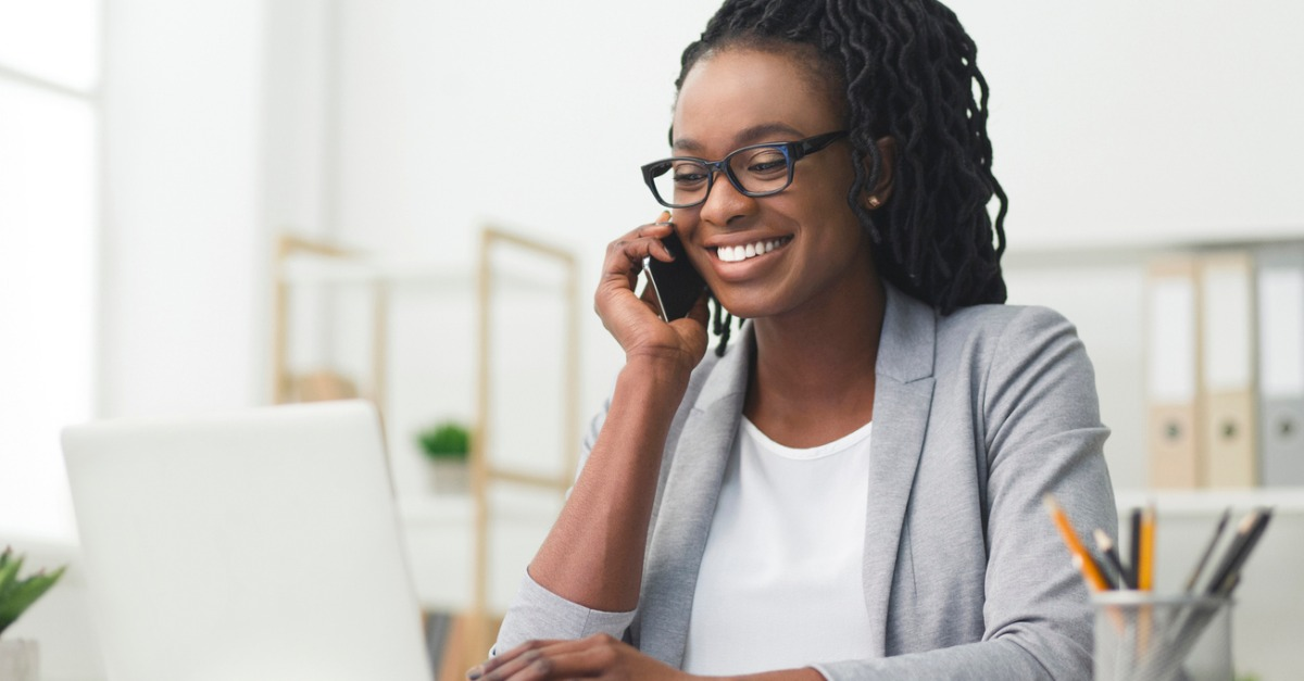 African American Business Woman Having Phone Conversation Working On Laptop In Modern Office, discussing how to use social media to build your personal brand.